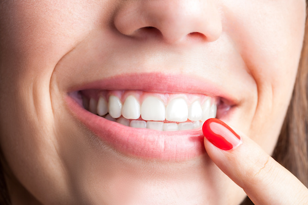 Extreme close up of woman pointing with finger at healthy teeth.