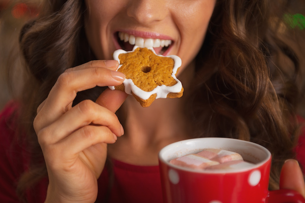 Closeup on happy young woman eating christmas cookie