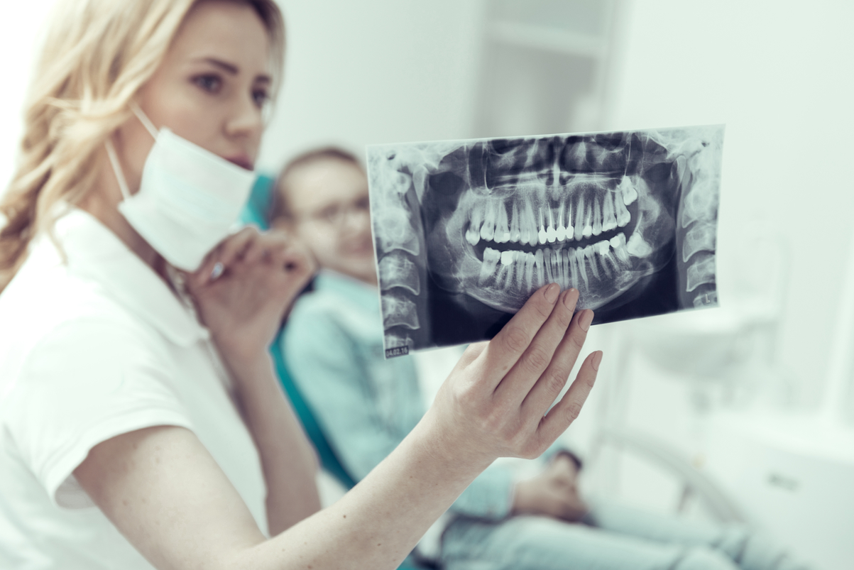 Good teeth. Professional young dentist studying the X-ray of a girls jaw