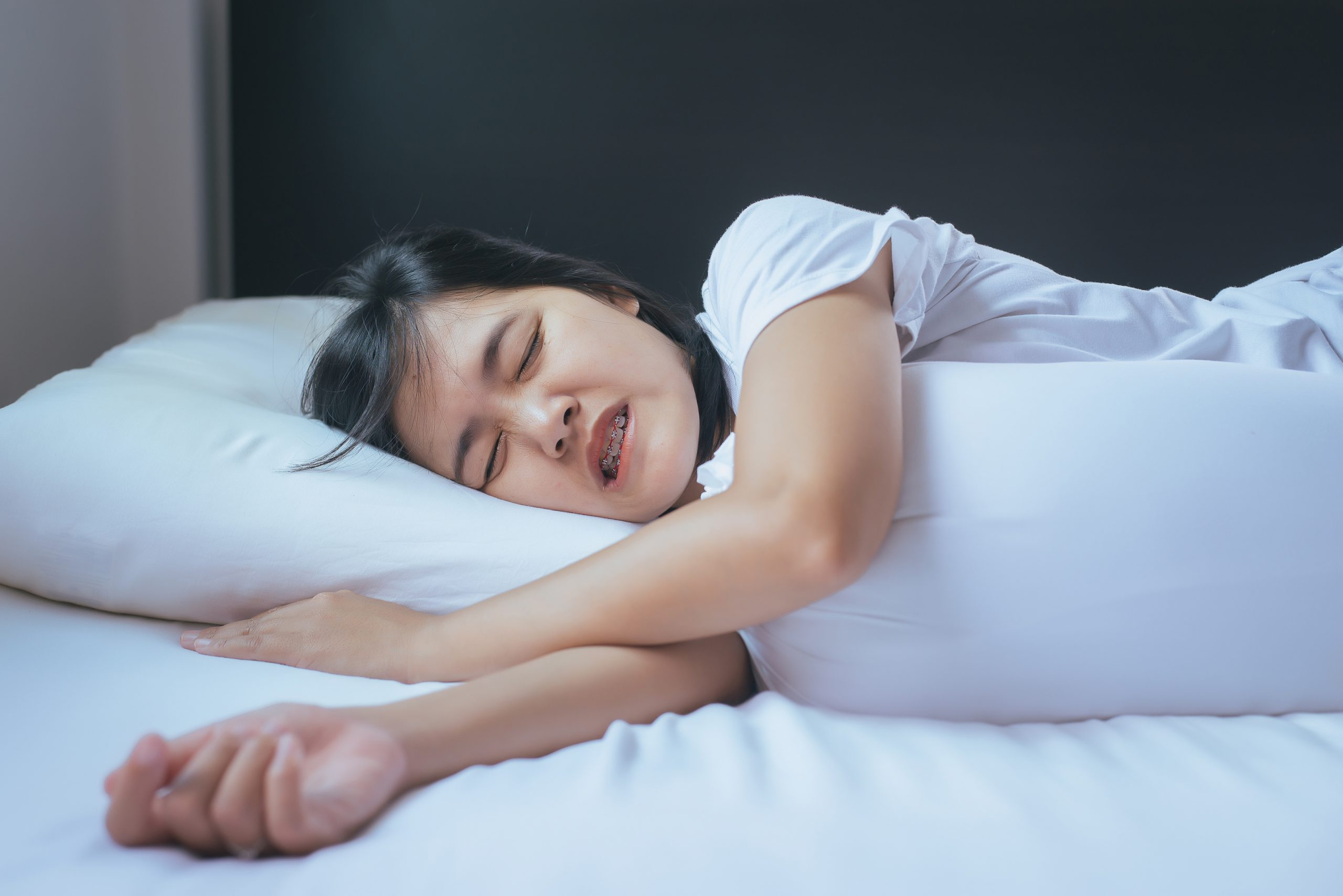 Female sleeping on the bed and grinding teeth,Tiredness and stress