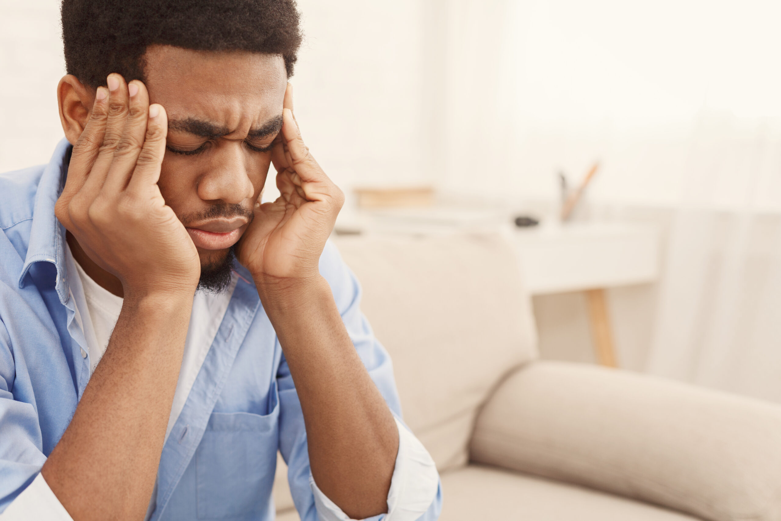 Exhausting migraine. Young african-american man suffering from headache at home, copy space