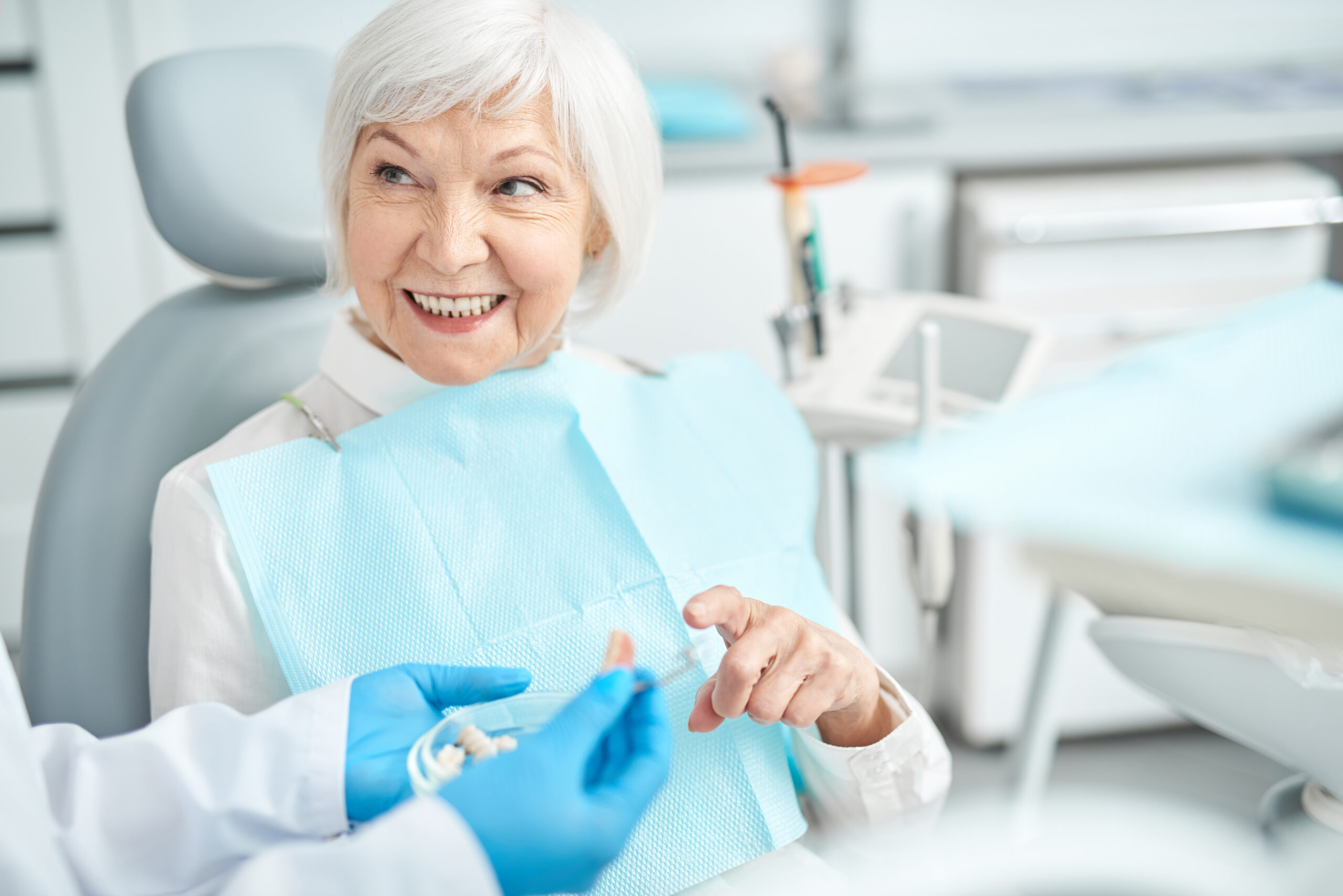 Smiling elderly woman looking at her doctor stock photo