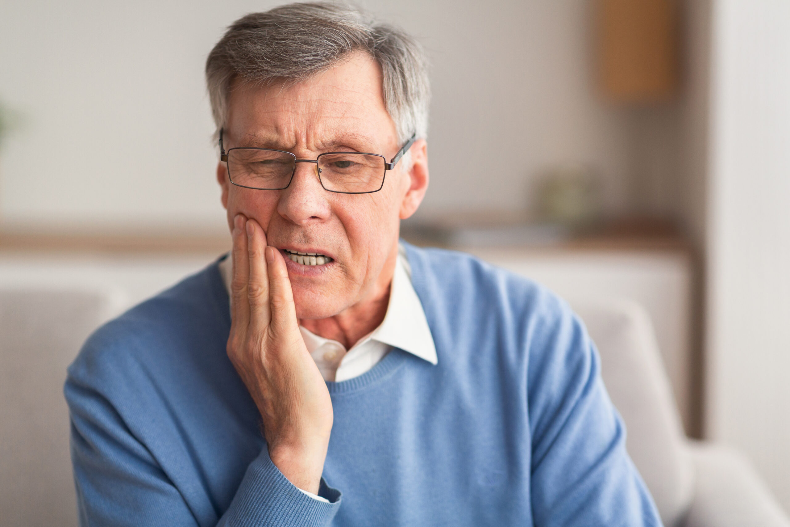 Tooth sensitivity is a common dental complaint that involves pain or discomfort in teeth when exposed to certain temperatures or substances. Elderly Man Having Toothache Touching Cheek Suffering From Pain Sitting On Sofa At Home. Selective Focus