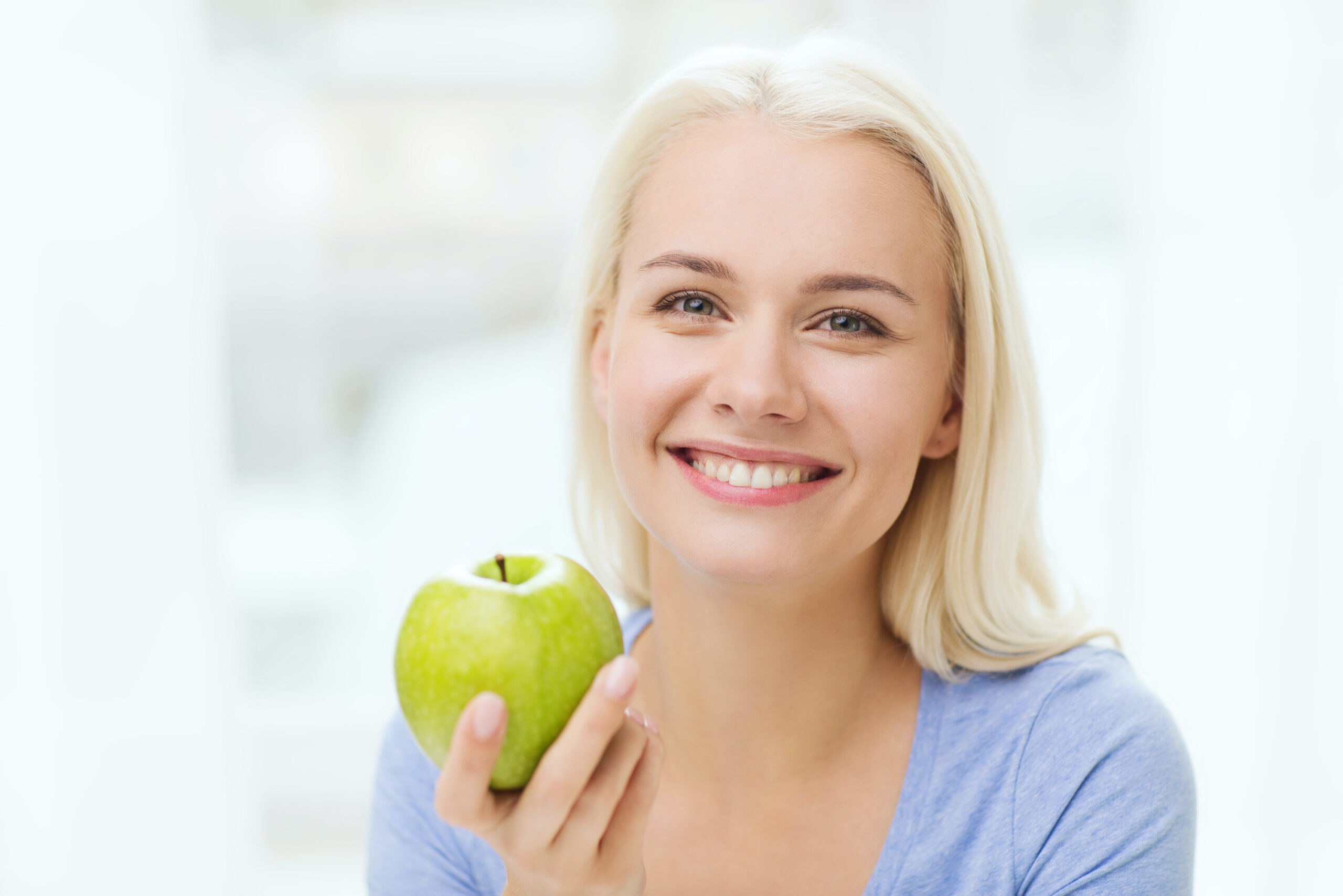 healthy eating, organic food, fruits, diet and people concept - happy woman eating green apple at home