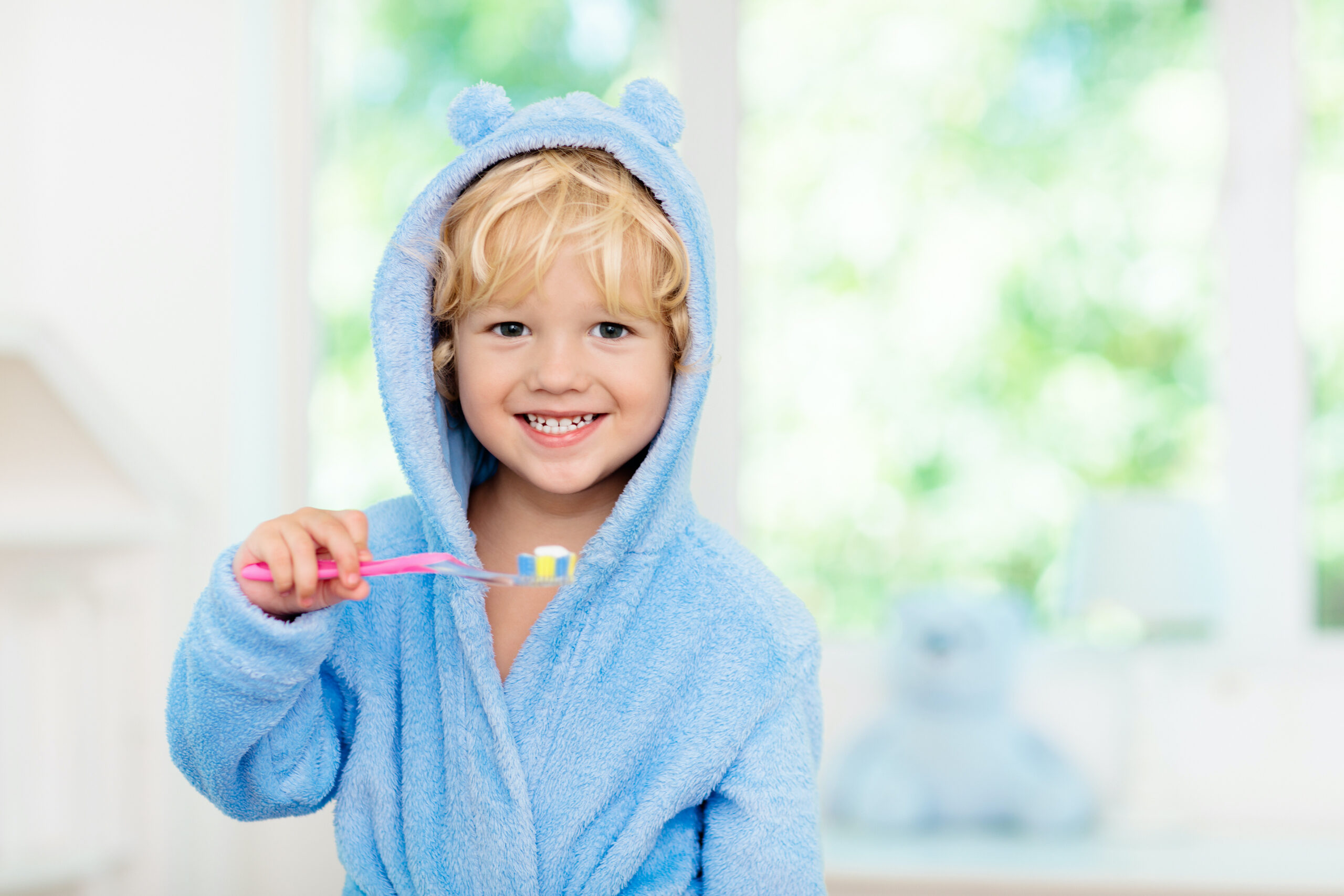 Child brushing teeth. Kids tooth brush and paste. Little baby boy in blue bath robe or towel brushing his teeth in white bathroom with window on sunny morning. Dental hygiene and heath for children. fluoride services