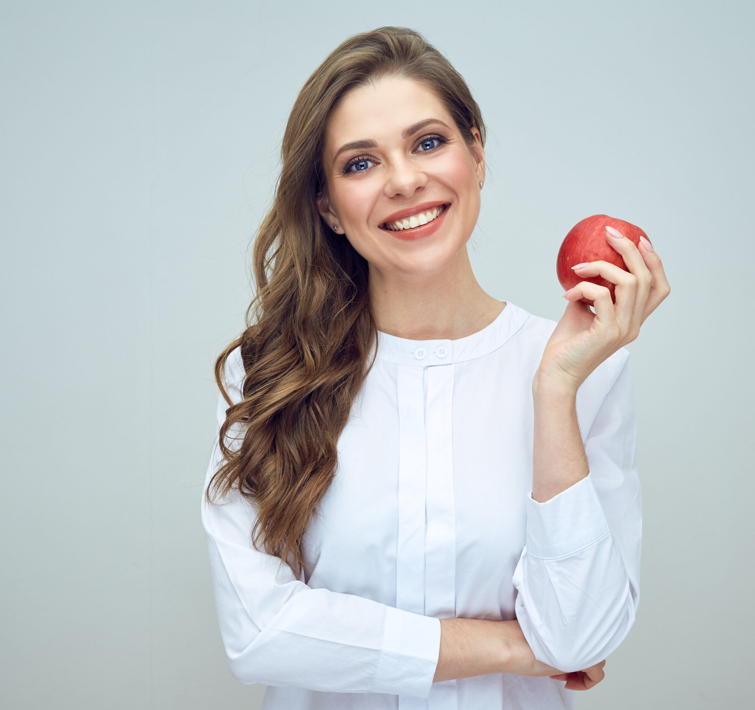 woman with toothy smile wearing white shirt holding red apple. isolated studio portrait. diet and teeth