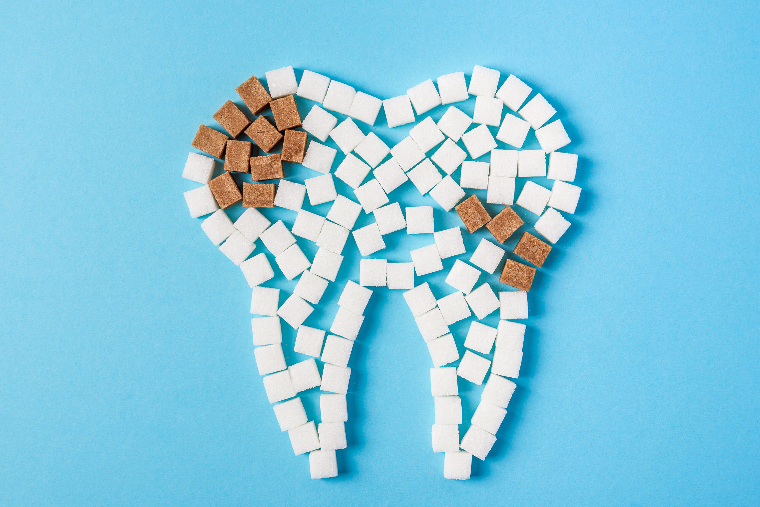 Sugar destroys the tooth enamel and leads to tooth decay. Tooth made of white sugar cubes and caries made of brown sugar cubes. Top view. Close up