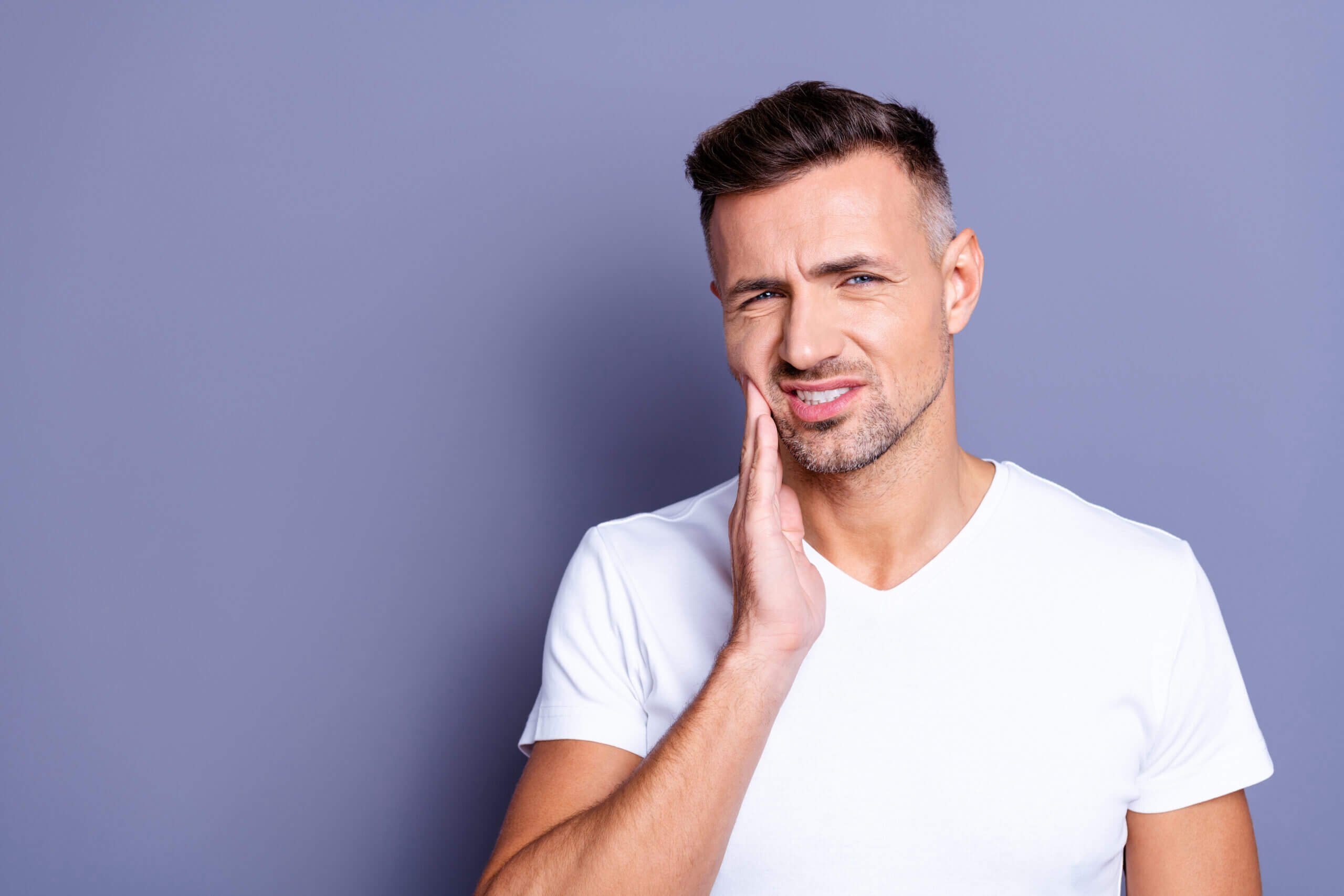 crack a tooth Close up photo amazing he him his middle age macho hand arm hold cheekbone, teeth terrible pain injury sadness cry facial expression weakness wear casual white t-shirt isolated grey background